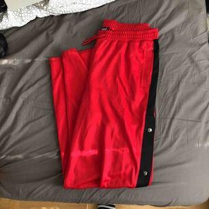 Röda byxor från Urban Outfitters. Knappar längs sidan. Bra skick använd fåtal gånger.