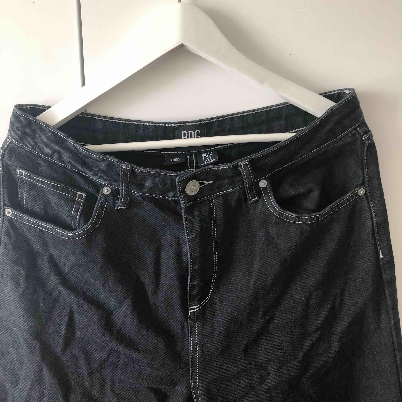 Mått- W32 L32. Snygga svarta utsvängda jeans med vita sömmar från Urban Outfitters. Korta i längden. . Jeans & Byxor.