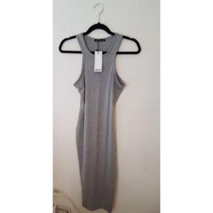 Enkel basic tajt klänning. Oanvänd med tags kvar. Frakt tillkommer