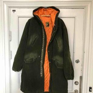 Vintagekappa i Manchester med huva och snyggt orange innertyg. Varm och mysig. Sannolikt från slutet av 80-talet. Funkar även som liten large då den är stor i modellen.