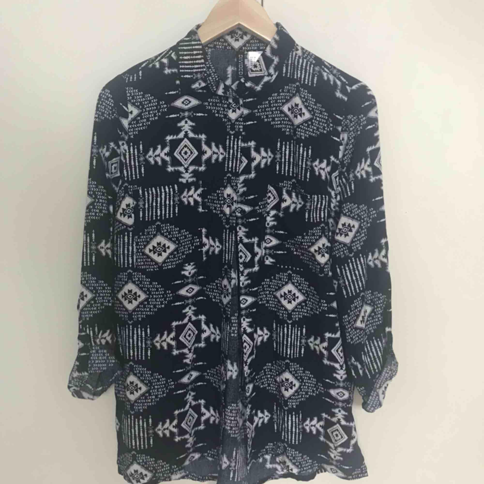 Marinblå/vit mönstrad blus, endast använd en gång. Inköpt på H&M, storlek 36.  💌 frakt är inräknat i priset. . Blusar.