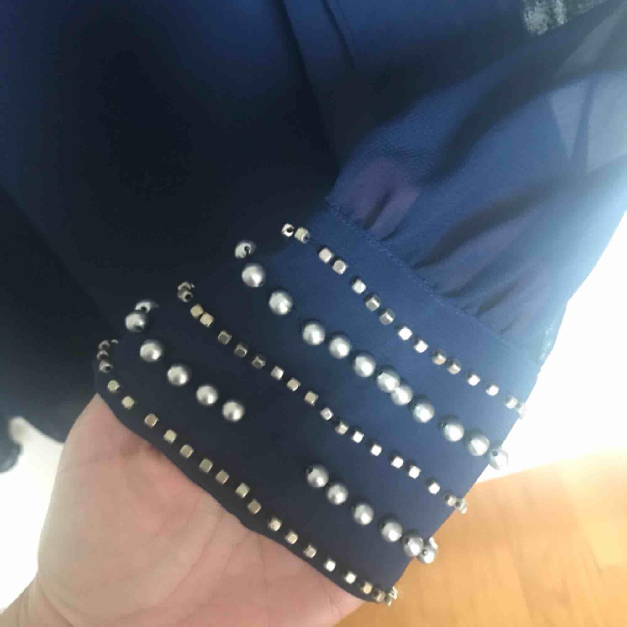 Marinblå blus med pärlor på ärmarna. Lite mer transparent tyg på armarna. Saknas två pärlor, se bild 3. Därav billigt pris. Inget som syns då det är närmst kroppen 💌 frakt är inräknat i priser . Blusar.