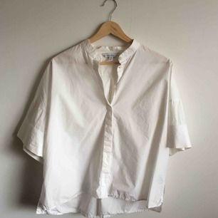 Vit croppad skjorta i krispig bomull. Använt skick, liten fläck på höger bröst (bild 3) i övrigt okej. Priset inkluderar frakt!