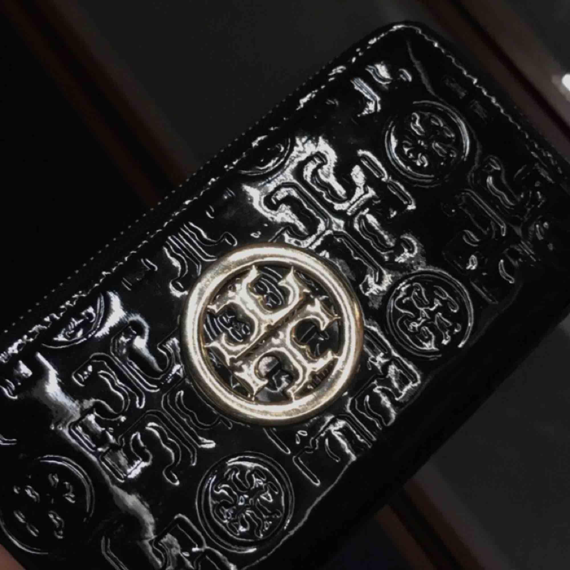 En söt svart plånbok från Tory Burch (kopia) med gulddetaljer. Väskor.