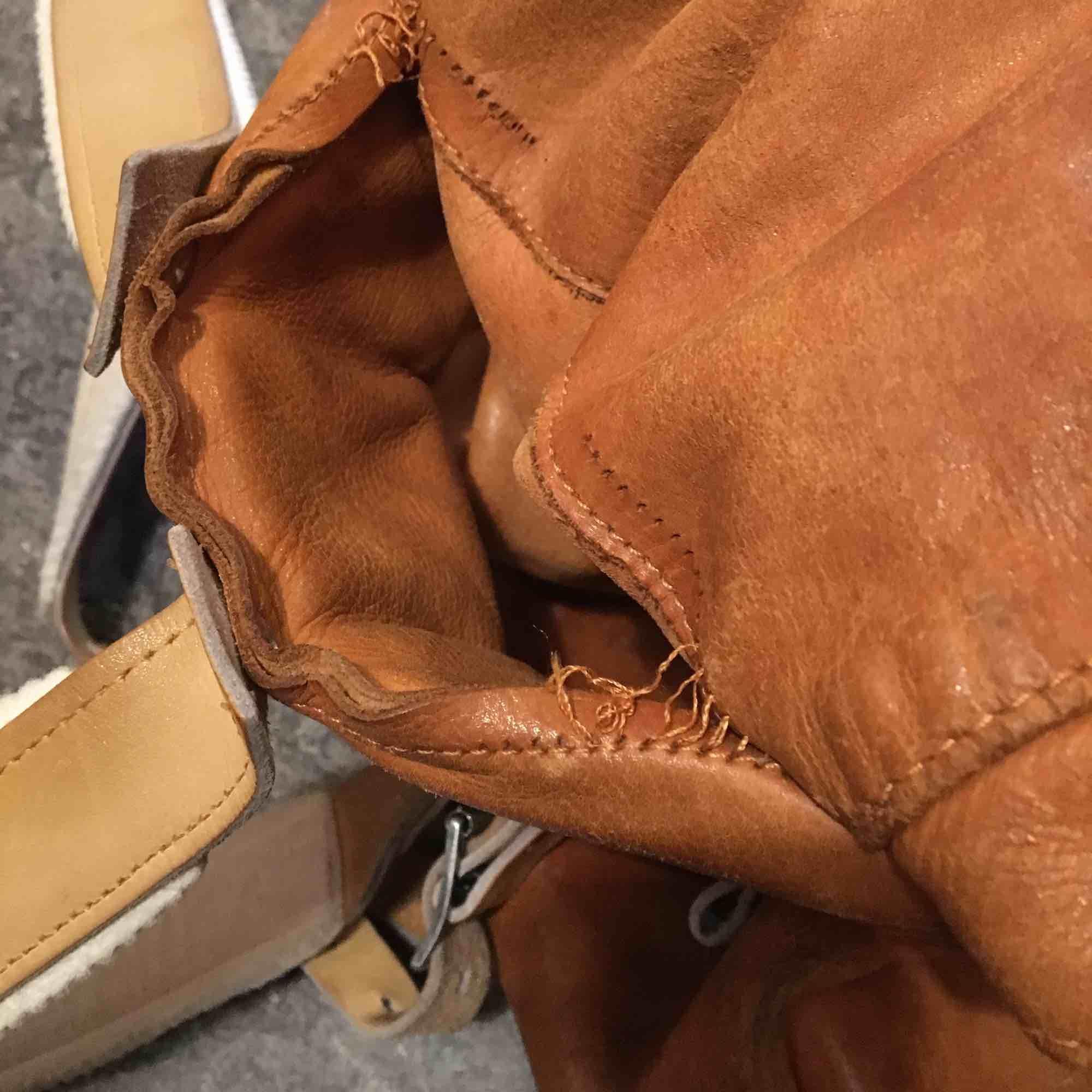 Fin läderryggsäck, men med sina små skavanker. En söm har börjat släppa lite, men den har gått att lasta rätt tungt ändå. Vet inte exakt volym, men gissar på ca 20 liter.. Väskor.
