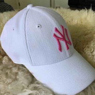 En vit New Era keps med ett rosa märke på. Aldrig använt! Kan både mötas upp i Sthlm eller posta.