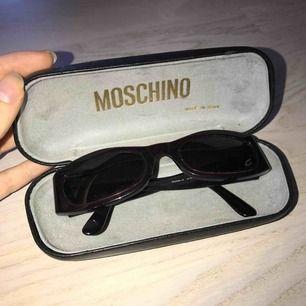 Snygga solglasögon från Moschino i en väldigt mörkröd, nästan svart, färg. Glasen är lite tonade i blått. Har inte kommit till användning. Begagnat fint skick! Äkta!!!