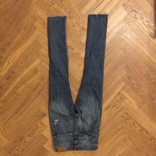 Ett par blåa högmidjade jeans med hål i från H&M i strl S.