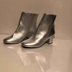 Ett par silver glittriga boots, nästan oanvända men har litet märke på ena hälen som du ser i andra bilden. Väldigt bekväma.