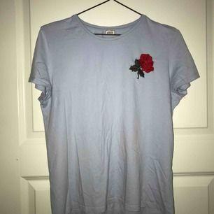 Ljusblå t-shirt med en ros på vänstra sidan. Använt ett flertal gånger, inte struken. (några fläckar/missfärgningar på baksidan men går bort i tvätten, syns ej under dagtid) MÖTS I STOCKHOLM!