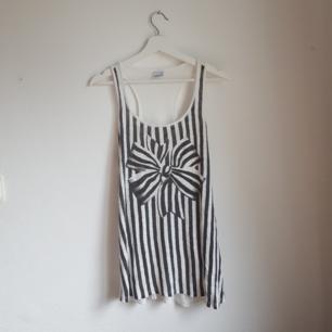Långt svartvit-randigt linne med helvit rygg. Storlek L. Bra skick och knappt använd!
