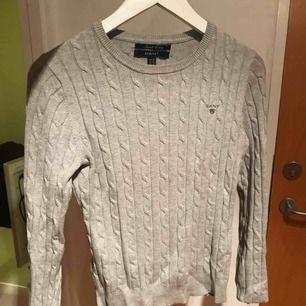 Grå kabelstickad u-ringad tröja från gant, använd en del men fortfarande i väldigt fint skick! Köparen står för frakt, skriv för fler frågor! :D