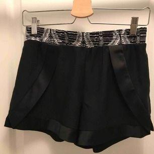 Fin-shorts med detaljer från Vila. Shortsen har mönster vid midjan och glansigare material på sidorna och botten, finns även fickor. Storlek S. Kan postas men då står köparen för frakten.