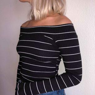 Långärmad randig tröja med öppna axlar i mörka höstliga färger. Köpt i USA.