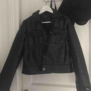 Säljer min jacka från lindex! Har använt den en gång i våras. Mycket bra skick.  Materialet är lite speciellt, la in en bild med blixt för att man ska se lite tydligare vad det är för material. Jackan har stora silvriga knappar.  Köparen står för frakt!