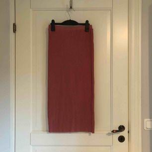 Lång, tight ribbad kjol ifrån Na-Kd. Är ca 165-170cm lång och den går till mitten utav mina smalben. Den är i en fin gammelrosa färg och är i ett strechigt tyg. Använd en gång. Köparen står för frakten.