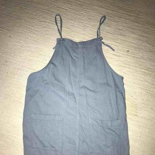 Klänning från Monki med justerbara axelband och fickor i fram.