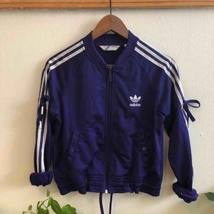 """Adidas Jacka i härlig lila färg, haft den i flera år men knappt använd. Jag är storlek 36 men tycker denna sitter jättebra trots att den är 40. Man kan dra åt i midjan o ärmarna för en intressant """"bomber look""""."""