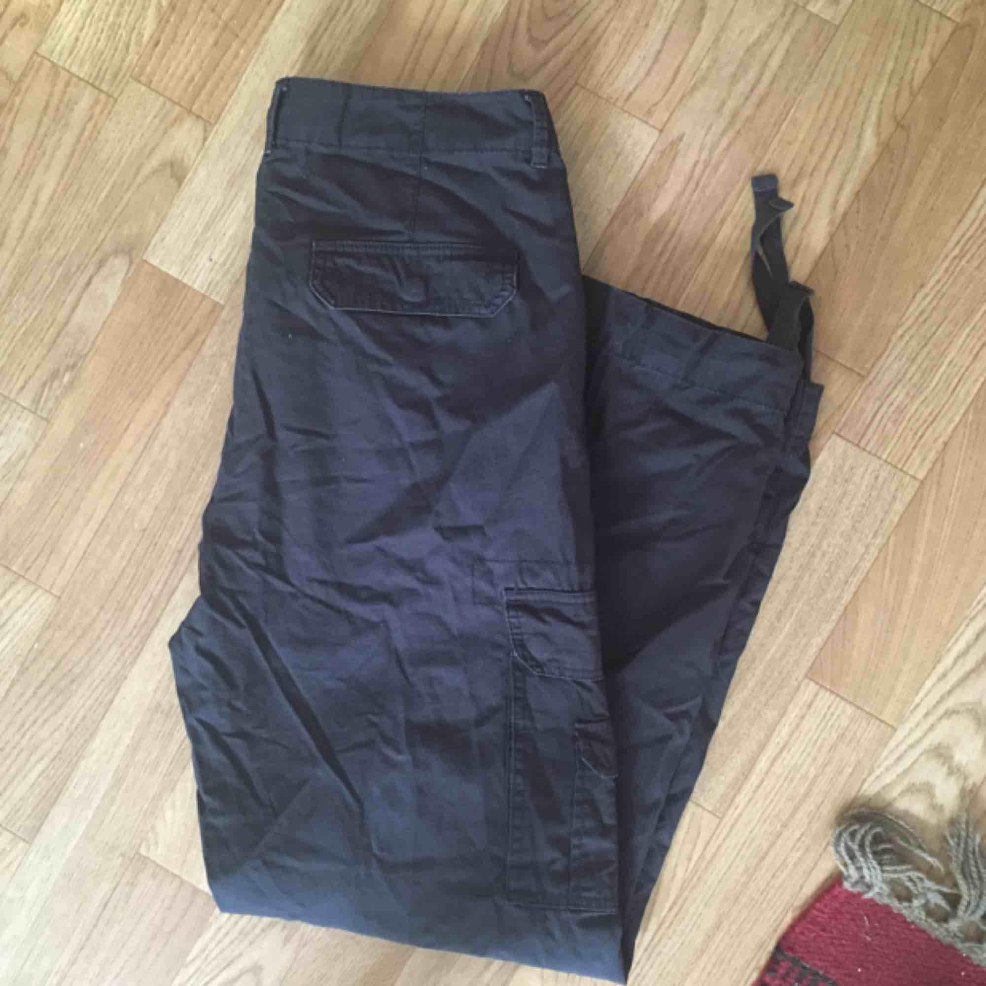 d989b39fb Cargobyxa med fickor på benen, mörkgrå-svarta. Stängs knapp + dragkedja och  har ...