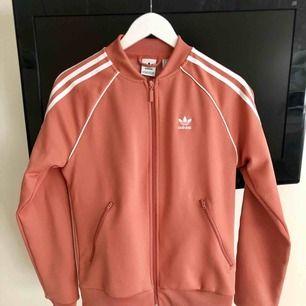 Säljer min snygga jacka från Adidas, använd en gång så i perfekt skick och som helt ny. Fin korall rosa färg med vita detaljer, frakt inräknat!
