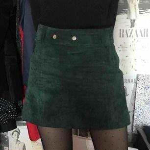 Kjol i smaragdgrön färg i mocka från Zara. Nypris 500. Knappt använd. Silvriga knappar.