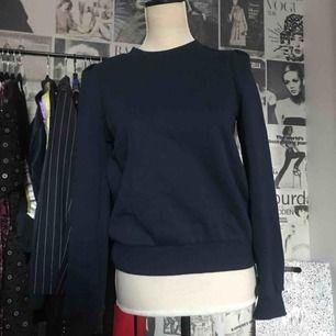 Marinblå sweatshirt med rynkade axlar som ger en gullig effekt. Köpare står för frakt.