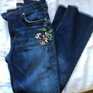 Ett par blåa ankeljeans från Zara med snygga blomdetaljer.  Byxorna är i storlek 34 eller XS och har endast använts två gånger.