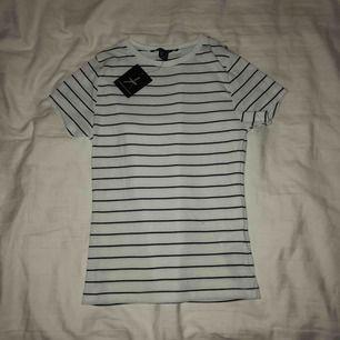 Vit t-shirt med svarta ränder från Primark , aldrig använd bara testad, en liten blå tråd är på tröjan som man ser på bild nr 3, men är ingenting som syns mycket. (Köparen står för frakten)