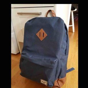 Herschel ryggsäck i marinblå färg med bruna läderdetaljer. Frakt 80 kr.