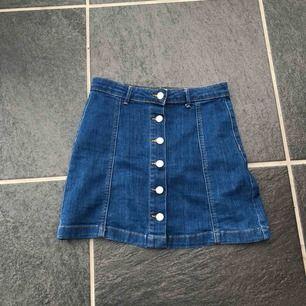"""Blå jeanskjol från Ginatricot, med """"uppknäppbara"""" knappar hela vägen. Knappt använd och är i fint skick"""