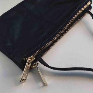 """Jättefin svart läderväska fån """"WERA Stockholm"""", väskan har """"två delar""""med mindre fack, justerbart axelband med guldiga detaljer. Ca 14x23cm."""