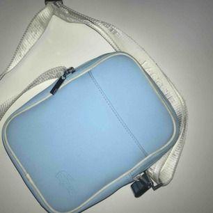 Skitcool äkta Lacoste väska.  Jättefin ljusblå färg med vitt 'band.  Säljer då den inte kommer till användning  BUDA!!