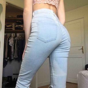 Högmidjade, jusblåa oanvända jeans med hål på knäna. Jag vet själv hur svårt det är att köpa jeans online så du får bestämma priset men lägsta/frakten är 55kr. Jag är 175cm lång och har 34 i jeans så därför sitter de lite loose