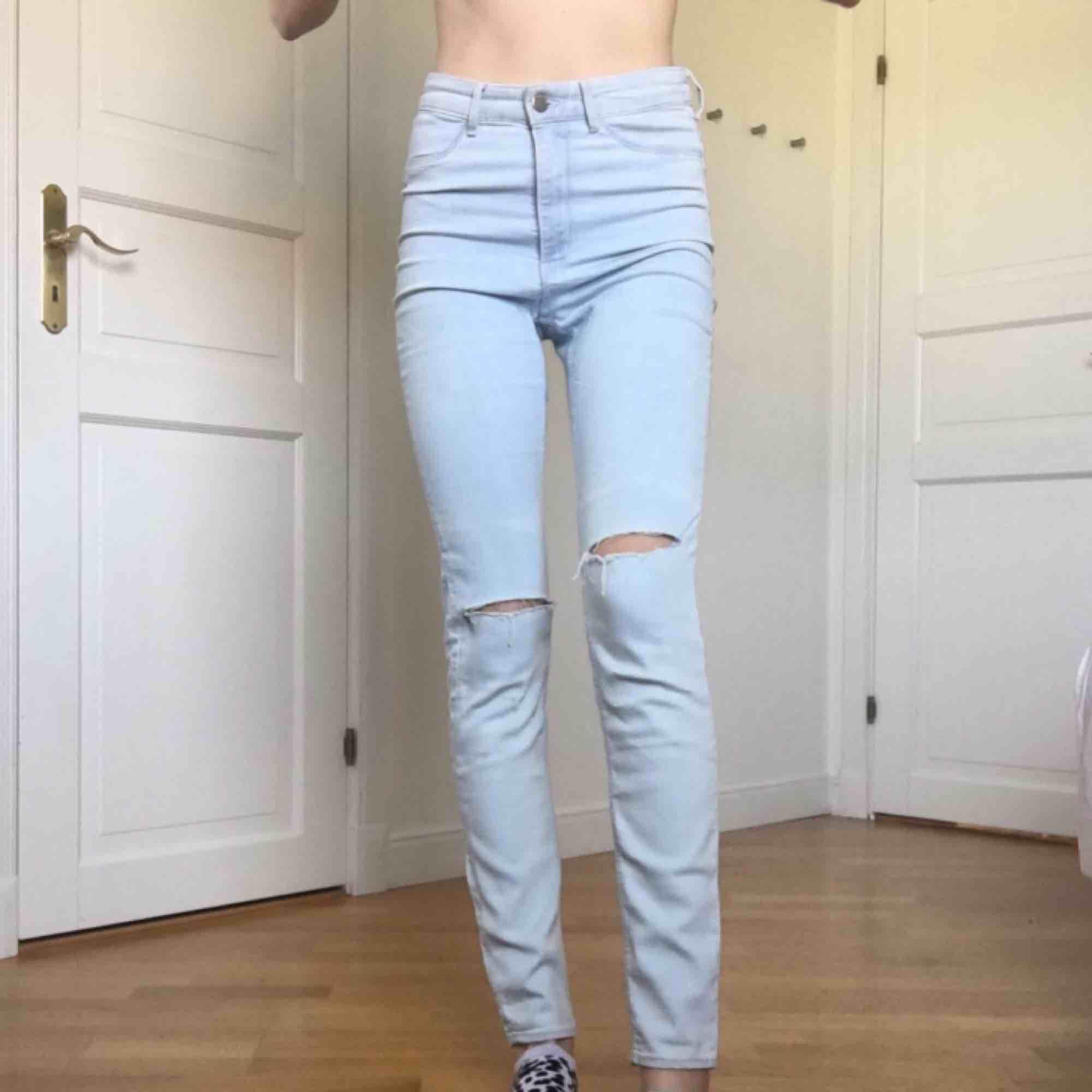 Högmidjade, jusblåa oanvända jeans med hål på knäna. Jag vet själv hur svårt det är att köpa jeans online så du får bestämma priset men lägsta/frakten är 55kr. Jag är 175cm lång och har 34 i jeans så därför sitter de lite loose. Jeans & Byxor.