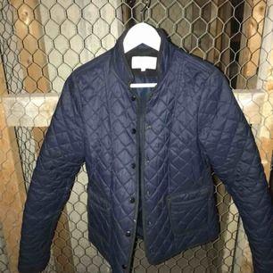 Mörkblå quiltad jacka med svarta detaljer.
