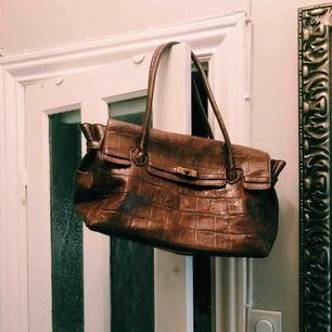 Superfin väska i brun fake-skinn. Bra med fack för mobil etc. på insidan. Använd ett fåtal gånger.