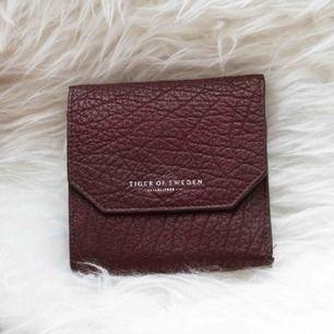 En sjukt snygg plånbok från Tiger Of Sweden i en rödbrun färg med textur. Många fack för kort, myntfack och även sedelfack. Nypris 800kr. Priset går alltid att diskutera!