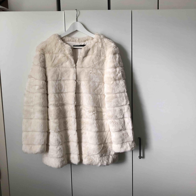 Vit fuskpäls från Zara. Väldigt mjuk och har ett silkesfoder på insidan. Har fickor och knappar, se bilder ovan.. Jackor.