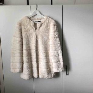 Vit fuskpäls från Zara. Väldigt mjuk och har ett silkesfoder på insidan. Har fickor och knappar, se bilder ovan.