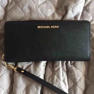 Svart plånbok med gulddetaljer från Michael Kors. Jättefin och rymlig. Den är helt oanvänd, har endast haft den i ett skåp som förvaring av kvitton och kort.