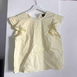 Super gullig gult linne med volanger vid ärmarna från lindex! Använd 1 gång så är i jättebra skick. Den är ej struken på bilden så bli ännu finare om man stryker den.