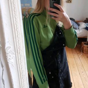 Grön Adidaströja med dragkedja. Den har några väldigt små hål därav det låga priset! (De märks ej om man inte kollar noga!) Även färgen på dragkedjan är lite bortskavd
