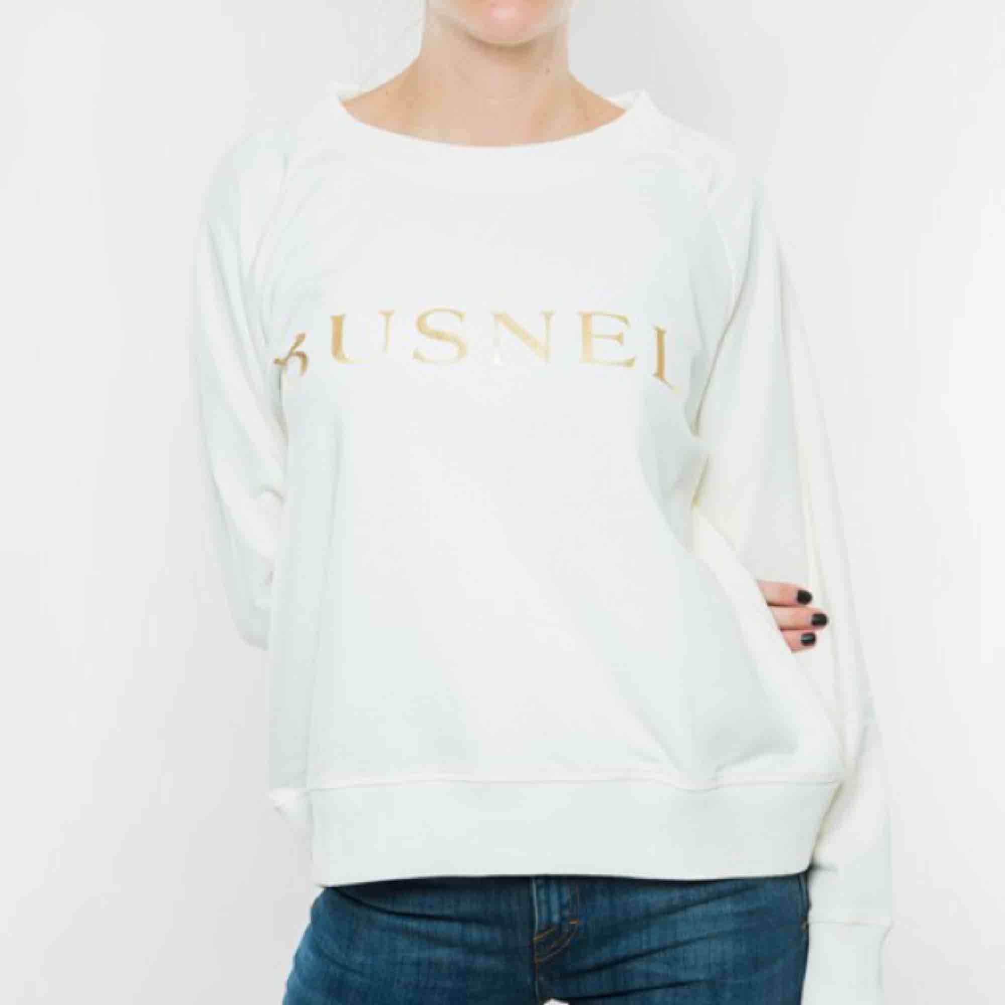 Vit sweatshirt med guldlogo i 100% bomull från Busnel. Relativt liten i storlek, passar S-M. Betalning via Swish, frakt på 58:- tillkommer.. Huvtröjor & Träningströjor.