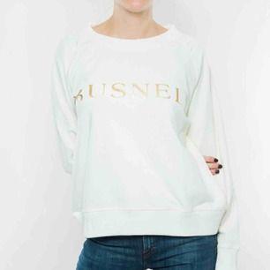 Vit sweatshirt med guldlogo i 100% bomull från Busnel. Relativt liten i storlek, passar S-M. Betalning via Swish, frakt på 58:- tillkommer.