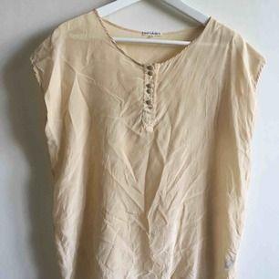 Beige perfekt sommar/office tshirt/blus i 100% silke. Storlek L men jag har haft den fastän jag drar typ 36.