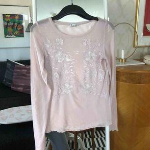 Rosa mesh-tröja med blommig detalj! Säljer pga använder inte, har bara använt nårra gånger.  Köpt på cubus förra sommarn, i fint skick!  Frakt ingår.