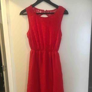 Röd klänning, kort fram/lång bak. Aldrig använd.