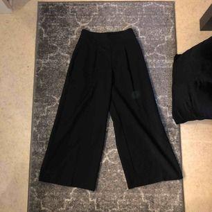 Vita svarta overknee långa byxor i kostymbyxe material. Ganska högmidjade med silvrig dragkedja på sidan