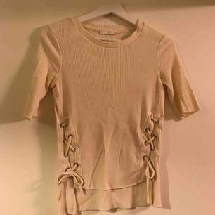 En creme-färgad tröja med snören vid sidan om.