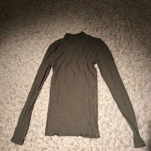 Långärmad, militärgrön, ribbad tröja. Fint skick.